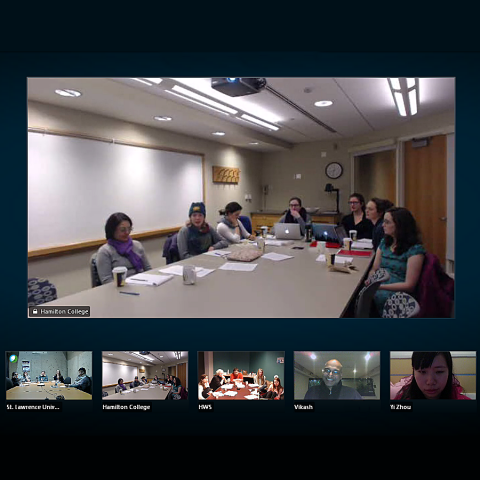 A group of students sit at a conference table while using video conferencing software.