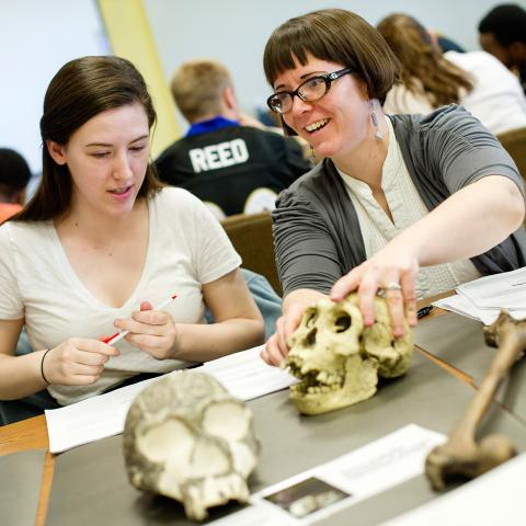 A student and professor sit at a desk, and the professor holds a skull.