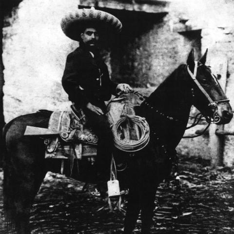A black and white photograph of a man sitting on a horse.