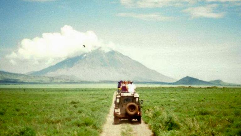 On a partly cloudy day, a vehicle is driving towards a mountain in Tanzania.